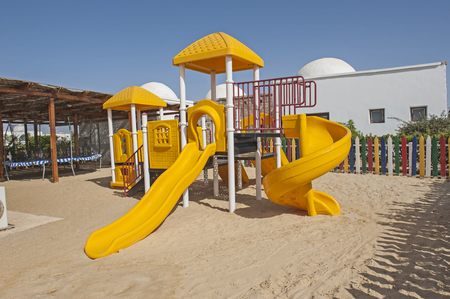 climbing frame: Chlildrens climbing frame with slide on sand in tropical hotel resort kids playground Stock Photo