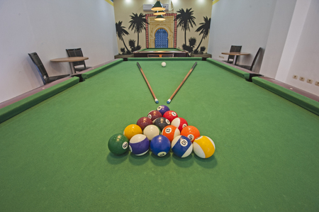 pool cues: Closeup of billiard balls on green felt table with pool cues in games room Stock Photo