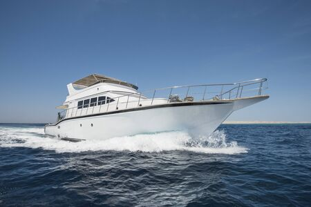 Luxury motor yacht boat sailing under way on tropical ocean with bow wave