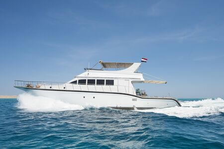 bow of boat: Luxury motor yacht boat sailing under way on tropical ocean with bow wave