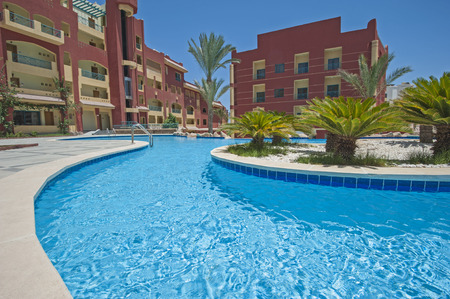 date palm: View over a swimming pool in luxury tropical hotel resort with date palm trees Stock Photo