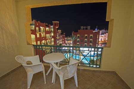 date palm: View over a swimming pool in luxury tropical hotel resort at night with date palm trees