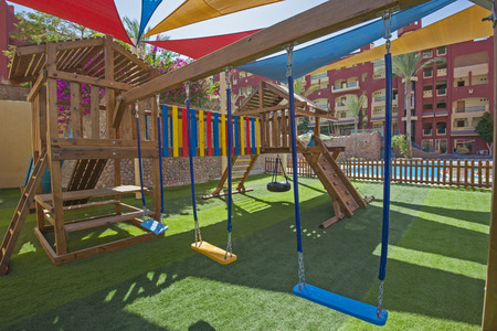 climbing frame: Childrens outdoor playground area at tropical hotel resort with climbing frame and swings Stock Photo