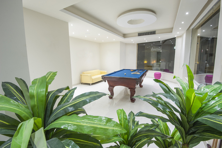 Interior design of a leisure games room in hotel with billiards pool table and plants