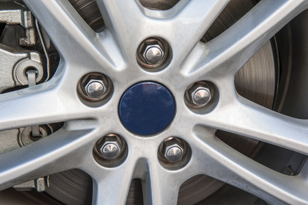 Closeup detail of a wheel hub on car tyre with nuts and brake disc