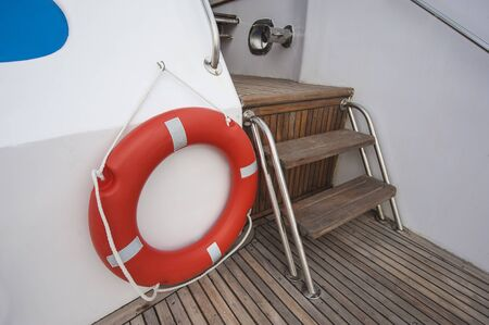 safety buoy: Safety equipment life buoy ring next to steps on teak deck of a luxury motor yacht Stock Photo