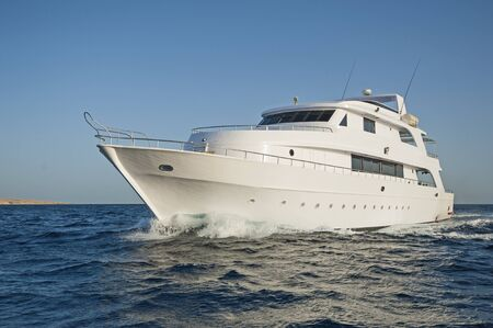 Large private luxury motor yacht boat under way sailing out at sea