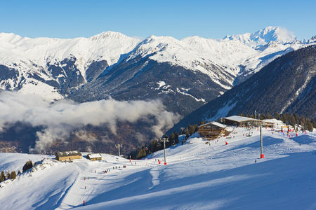 Panoramic view down snow covered valley in alpine mountain range with clouds Standard-Bild