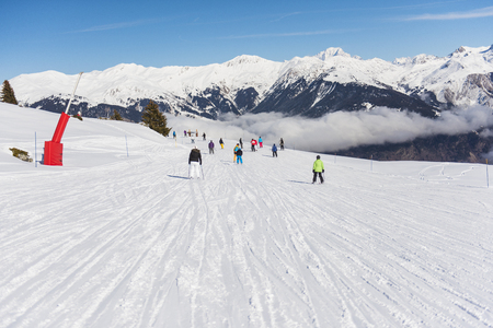 Skiers on a ski slope piste in winter alpine mountain resort