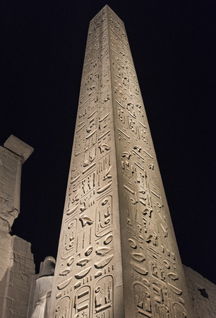 obelisk stone: Tall stone ancient egyptian obelisk at Luxor Temple lit up in night on black sky background Stock Photo
