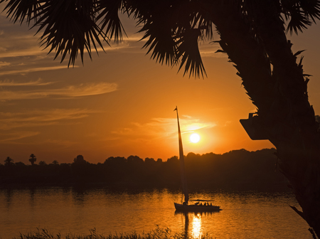 Traditional egyptian felluca sailing boat on river Nile in silhouette at dusk sunset Stock Photo