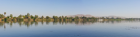 Panoramic landscape rural countryside view of large river nile in arid environment showing luxor west bank