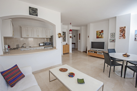 open floor plan: Kitchen lounge and dining area in luxury apartment show home showing interior design decor furnishing