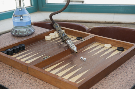 Closeup of backgammon board game and shisha water pipe in traditional egyptian street cafe coffee shop Stock Photo
