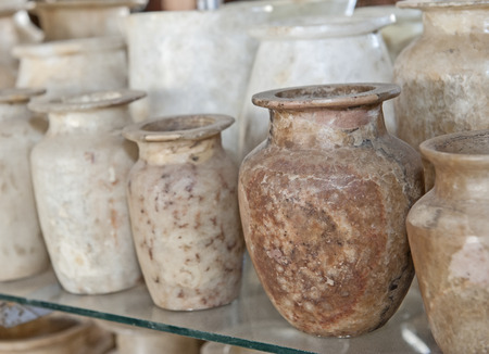Row of hand crafted alabaster jars and vases on glass shelf at an egyptian market shop stall