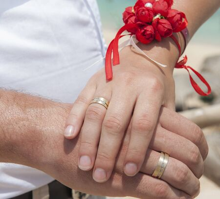 Newly married couple holding hands and showing off their wedding rings Stock Photo