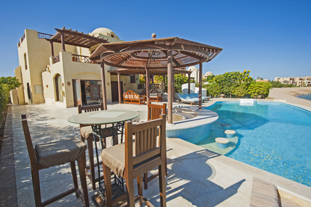 show window: Luxury villa show home in tropical summer holiday resort with swimming pool and sun chairs Stock Photo