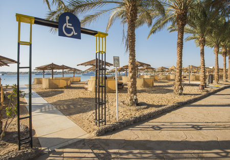 Landscape view of a sandy beach with disabled access and sunbeds at tropical luxury hotel resort Stock Photo
