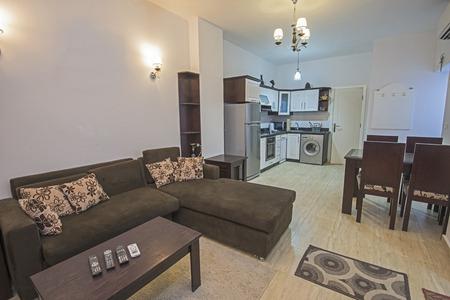 Decoración de diseño interior de un apartamento de planta abierta, cocina  con muebles y mesa de comedor.