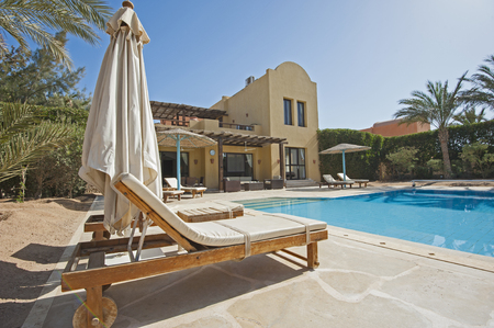 Luxury villa show home at tropical summer holiday resort with swimming pool and sun chairs in garden