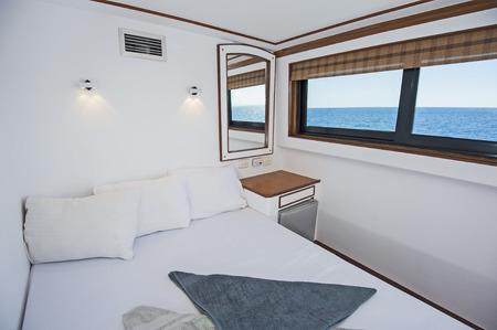 Letto matrimoniale nella cabina di un lussuoso yacht a motore privato Archivio Fotografico - 95927179