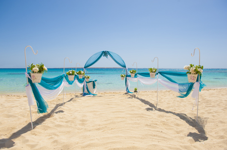 Aisle at a tropical island beach wedding ceremony setup with signpost plants and ocean background