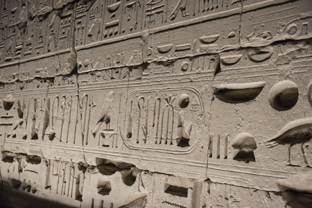 Stone ancient egyptian wall covered with hieroglyphics at Karnak Temple in Luxor lit up during night.