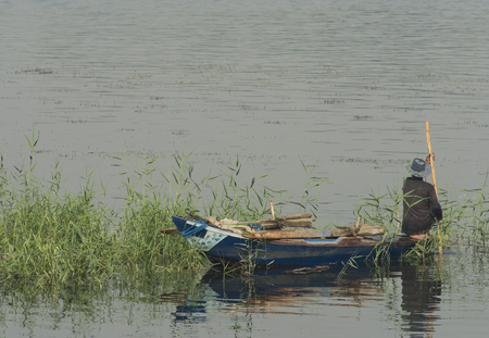 Traditional egyptian bedouin fisherman in rowing boat on river Nile fishing by riverbank grass reeds 写真素材