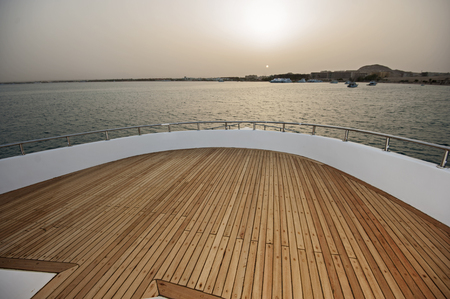 View over the bow of a large luxury motor yacht on tropical open ocean at sunset