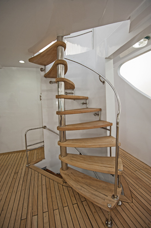 Wooden curved spiral staircase on sundeck area of large luxury motor yacht Foto de archivo