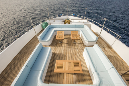 Bow Teak Deck Of A Large Luxury Motor Yacht With Chairs Sofa Table And  Tropical Sea