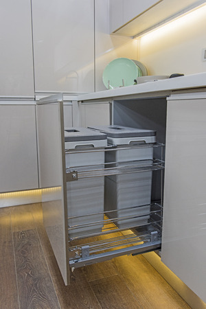 Interior design decor of kitchen in luxury apartment showing closeup detail of sliding cupboard with bins