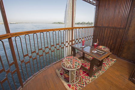 Seating chair and table on the cabin balcony of a luxury nile river cruise boat with panoramic view Imagens