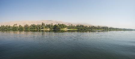 Vista panoramica sul grande e ampio fiume Nilo in Egitto attraverso il paesaggio di campagna rurale e lo sfondo di montagna