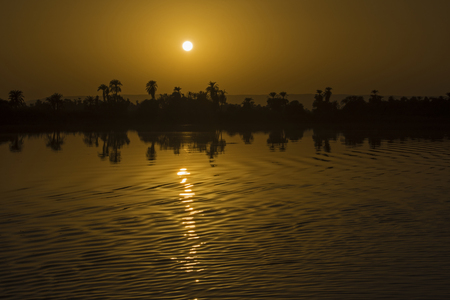 View across large wide river Nile in Egypt through rural countryside landscape with beautiful orange sunset