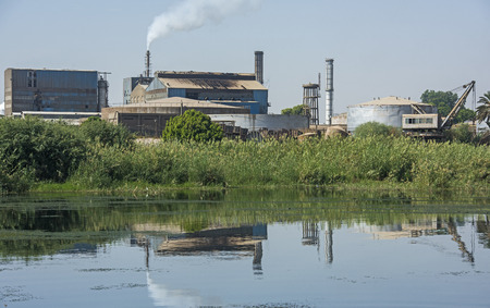 View across large river Nile in Egypt through rural landscape with indutrial sugar cane factory causing pollution