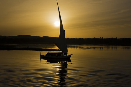 Silhouette of traditional egyptian felluca sailing boat on river Nile with reflection at Aswan in evening dusk orange sunset