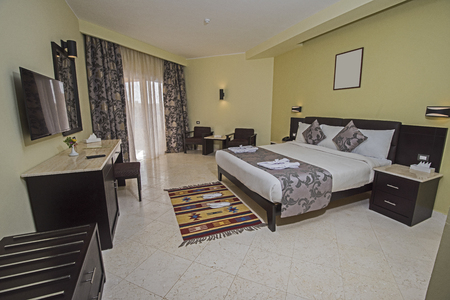 Double bed in suite of a luxury hotel room with patio door and curtains Stockfoto