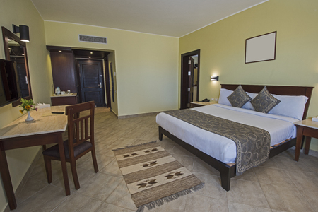 Double bed in suite of a luxury hotel room with adjoining area