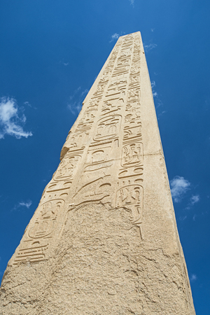 Large tall ancient egyptian obelisk at the temple of Karnak in Luxor with hieroglyphic carvings on blue sky background Archivio Fotografico