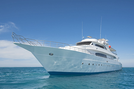 Large luxury motor yacht under way sailing out on tropical sea ocean with blue sky background Imagens