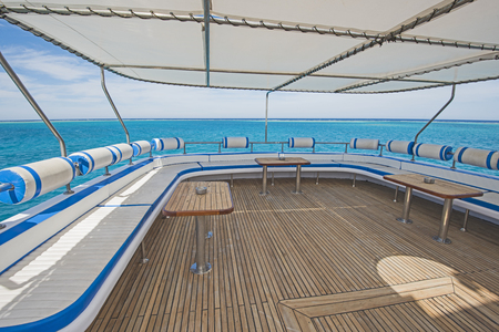 Sundeck area of a large luxury motor yacht with chairs sofa table and tropical sea view background Reklamní fotografie