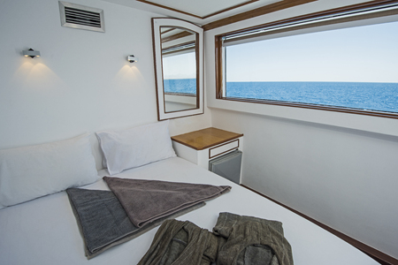 Double bed in cabin of a luxury private motor yacht with sea view