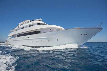 Large luxury motor yacht under way sailing out on tropical sea ocean with blue sky background Banco de Imagens