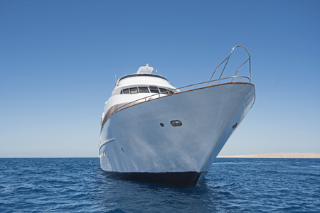 Bow of large luxury motor yacht sailing out on tropical sea ocean with blue sky background