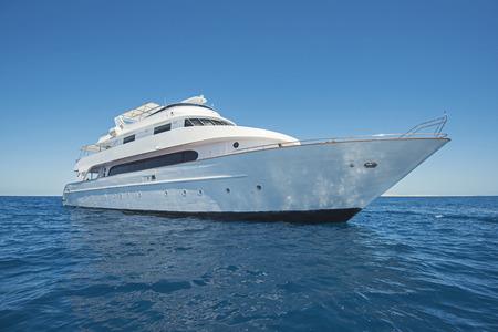 Große Luxus-Motoryacht, die auf tropischem Meer mit blauem Himmelshintergrund segelt Standard-Bild