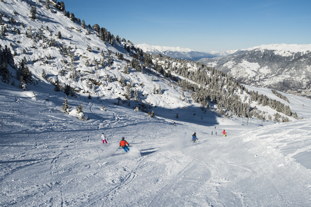 Panoramic landscape valley view with skiers going down a ski slope piste in winter alpine mountain resort