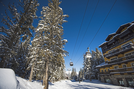 Panoramic view of a snow covered ski piste and trees in an alpine resort with cable car lift and hotel 免版税图像