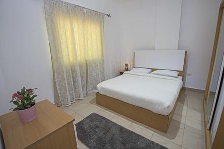 Cama doble en el dormitorio del apartamento de lujo que muestra el diseño de interiores
