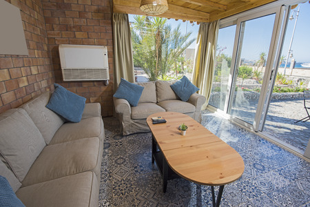 Living room lounge in luxury holiday villa show home showing interior design decor furnishing and open plan design with garden view Archivio Fotografico